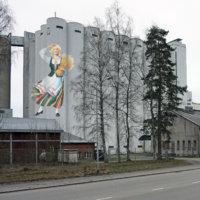 Elovena-neito tervehtii pian ohikulkijoita Nokian myllyn viljasiilojen kyljestä
